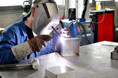 Welder works in a metal construction company. Detail photo with workmen and interieur Stock Photo