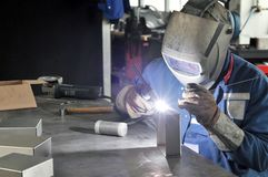 Welder works in a metal construction company. Detail photo Stock Images