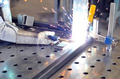Welder works in a metal construction company. With welding machine Stock Photo