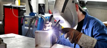 Welder works in metal construction - construction and processing. Of steel components royalty free stock photo