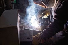 Welder in workshop conditions sample weld from sheet metal to un Royalty Free Stock Photo