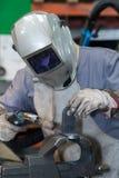 Welderen i maskeringssvetsningmetall och gnistor belägger med metall tätt royaltyfri foto
