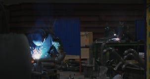 Welderen i svetsande maskering, i arbetekläder på fabriken, svetsar röret i fabriksrummet stock video