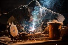 Welderen ?r svetsningmetalldelen i fabrik arkivbilder