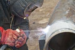 Welderen utför svetsningarbeten på rörledningrostfritt stål Arkivbild