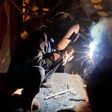Welderkonstruktion i den industriella fabriken Arkivfoton