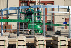 Welders on Lift. Construction welders working from lift with capstones in foreground Royalty Free Stock Photo