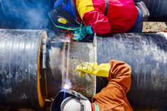 Welders working on a pipeline. Welders with protective equipment welding outdoors pipeline construction Stock Images