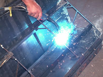 Welding. Sparks and blue light of welding a steel frame Stock Images
