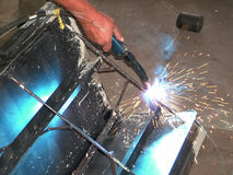 Welding. Sparks and blue light of welding a steel frame royalty free stock images
