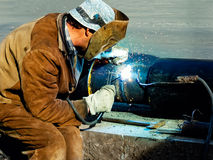 Welding. Metal worker welds two pieces of metal together Stock Photography