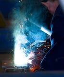 Welding. Boilermaker welding steel in a metl fabrication factory throwing off blue light around him as he works stock image