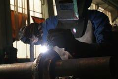 Welding. Worker welding metal pipe in workshop Stock Photography