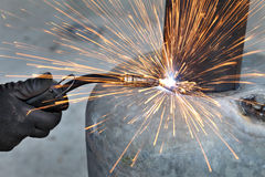 Welding. Arc welding of a steel, welder hands in gloves, tool and sparks Royalty Free Stock Photography
