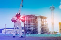 Welding construction. Worker man welding steel construction for fire line pipe in workshop of project site double exposure concept Royalty Free Stock Photo
