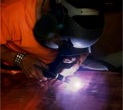 Welding on Copper Plate. Man in welding mask working on a copper plate Stock Images