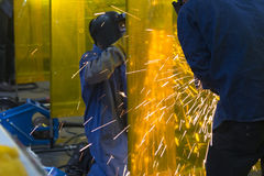 The welding craftsman grinding the steel tube Stock Photos