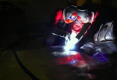 Welding in dark. Two welders wearing protective gear working in darkness Stock Photo