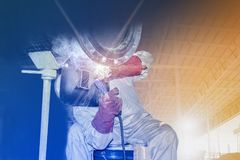 Welding factory. Worker man welding steel construction for fire line pipe in workshop of project site double exposure concept Stock Photography
