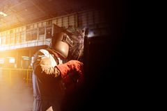 Welding factory. Worker welding metal piping using arc welder and wear equipment protection mask in factory on dark tone Stock Photography