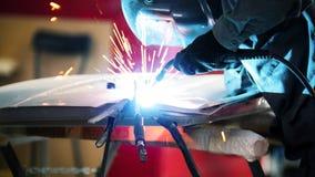 Welding industrial: worker in helmet repair detail in car service Royalty Free Stock Images