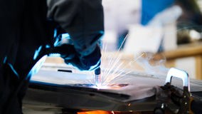 Welding industrial: worker repair detail in car service, close up Stock Image