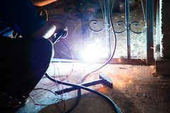 Welding iron. Worker welding electricity iron with many sharp sparks Stock Image