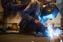 Welding iron workpieces. Young welder in protective mask leaning over workbench and welding iron workpieces royalty free stock image