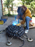 Welding Light. A woman wearing protective gear welds a metal art sculpture together Royalty Free Stock Photography