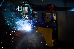 Welding machine and industrial worker on the plant. Close up of bright blue sparks. Stock Images