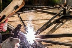 Welding metal construction close up. Welder Man Welding Spark Light Hot. Welder man welding, spark, light and hot. Metal, iron work, and work. Mask and gloves Royalty Free Stock Photo