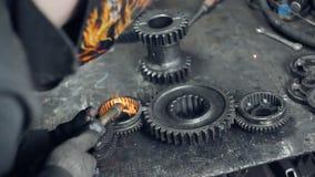 Welding of metal gears. Several metal gears lie on a metal table. Men`s hands welded metal gears together. Flying sparks