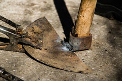 Welding old broken hoe with electrocautery. Welder repair old broken hoe Royalty Free Stock Photography