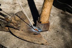 Welding old broken hoe with electrocautery. Welder repair old broken hoe Stock Image