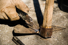 Welding old broken hoe with electrocautery. Worker welds broken Morico with electrocautery Stock Photography