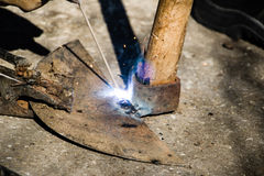 Welding old broken hoe with electrocautery. Worker welds broken Morico with electrocautery Royalty Free Stock Photo
