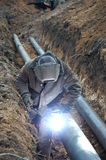 Welding operator. Is working with pipe in earthen hole Stock Photography