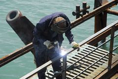 Welding operator and sea. Welding operator works on pier near the sea Royalty Free Stock Image