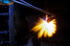 Welding a part, a worker heats a part with a gas torch, a smelting royalty free stock photo