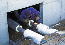 Welding pipes. Construction welder joining utility pipes stock photos