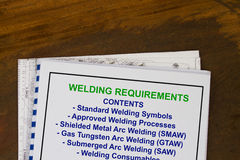 Welding requirements. Manual with blueprints in a wood texture background stock images