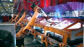 Welding robots on industrial factory stock video