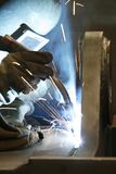 Welding Sparks. An factory worker with welding torch and protective mask Stock Image