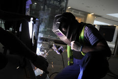Industrial welder at work. Industrial welder in protective clothing welding metal parts on construction site Royalty Free Stock Photo