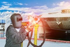 Welding steel. Double exposure welding workers,tig welding in ship yard and blue sky background Royalty Free Stock Photos