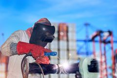 Welding steel. Double exposure worker welding on port with container background Royalty Free Stock Photo