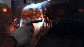 Welding steel with electricity in auto body repair shop, closeup stock footage