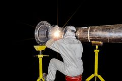 Welding steel pipe. Worker welding man arc welding steel pipe, siting back at workshop on black background in shipyard Thailand Royalty Free Stock Photography