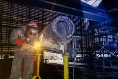 Welding steel pipe. Worker welding arc steel pipe at the factory made metal in factory  blue and dark tone Royalty Free Stock Image