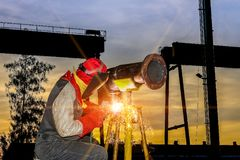 Welding steel piping. Worker welding metal steel pipe using arc welding, construction working in sunset sky black background Royalty Free Stock Photos